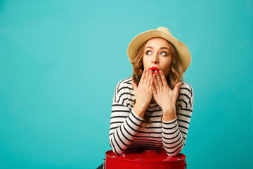 Portrait of young beautiful blond woman in hat with scary expression on her face over blue background