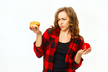 Portrait of young beautiful blond woman holding red apple in one hand and burger in another over white background