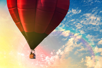 Hot air balloon flying over sky and rainbow with traveler.