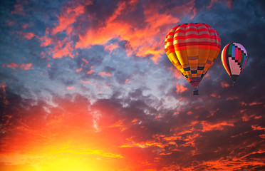 Hot air balloon flying over dramatic sky and colorful clouds