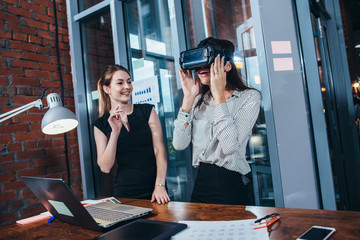 Two female application developers testing a new app designed for VR headset standing in modern office