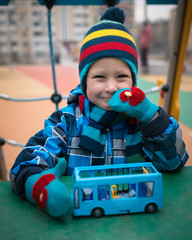 Cheerful little boy sits in front of a toy and smiles. Beautiful child playing with small car on the playground area in the winter