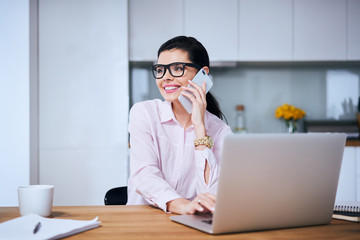 Cheerful woman talking on phone while working on laptop from home