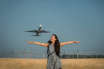 Female traveler is standing on the beach and looking on the aircraft. Jet plane takes off on the background behind a young woman. Funny girl spread her arms and ready for flyaway. Aircraft like a bird