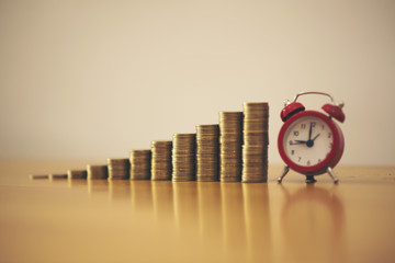 Stacking coins on desk with clock. Finance and money concept. Color tone