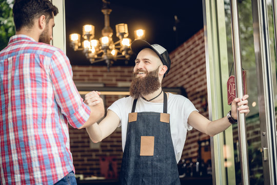 Low-angle view of a cheerful barber with hipster beard wearing an apron, while greeting his male customer at the entrance of a cool hair salon for men