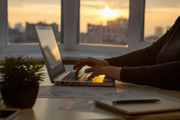 Business women work process. Marketing strategy brainstorming. Paperwork and digital in office. The windows are sunset.