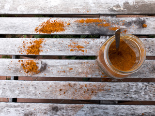 Shot taken from above of an open can, containing orange paprika, leaning against an old wooden table. The paprika was also sprinkled on the table.