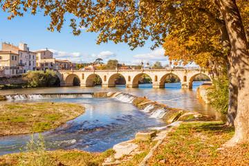 pont romain de Sommières sur la Vidourle et platanes en automne