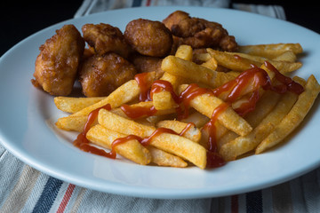A plate of french fries and chicken