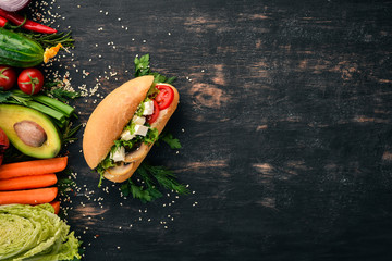 Burger, sandwich with feta cheese, mushrooms and lettuce leaves. On a wooden background. Top view. Copy space.