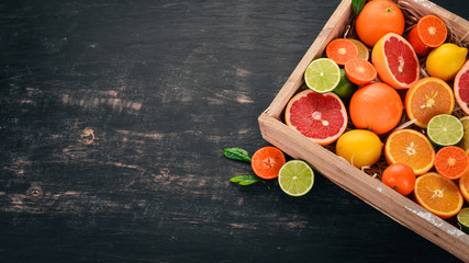 Assorted citrus fruit in a wooden box. Orange, tangerine, grapefruit, lemon. On a wooden background. Top view. Copy space.