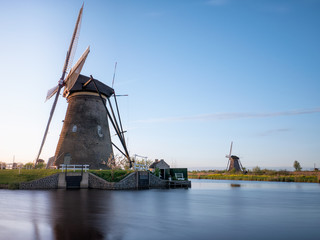 old iconic stone wind mill at the river in holland / netherlands, water reflection, blue sky and lots of room for text