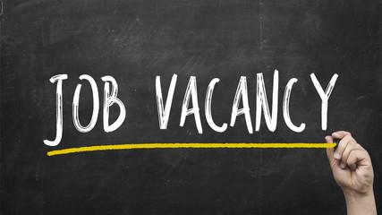 Hand writing Job vacancy on black chalkboard