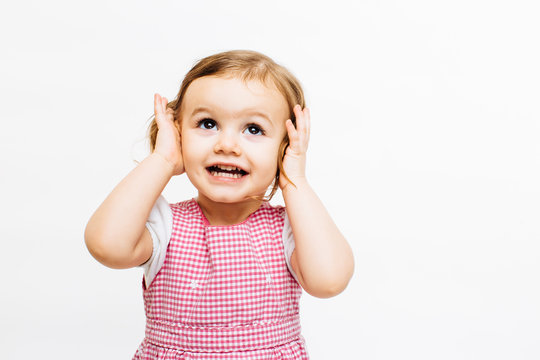 Preschool toddler girl with ponytails holding her ears and looking up isolated on white background