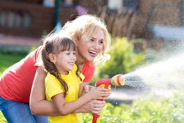 Pretty woman and her child daughter watering with hose in the garden