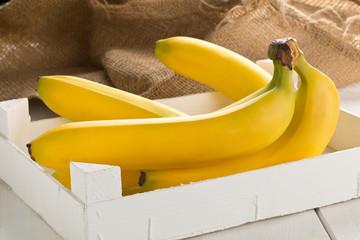 Bundle of fresh, yellow, ripe bananas in box
