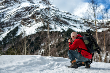 man photographer take  picture in the snowy mountains