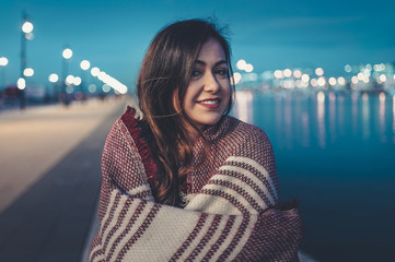 Portrait of smiling young woman standing on a promenade at dusk with a scarf and harbor bokeh lights