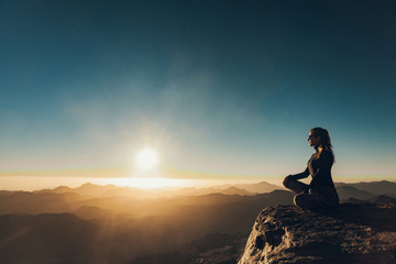 Woman sits in a pose of yoga on Mount Sinai and meditates against background of sunrise.
