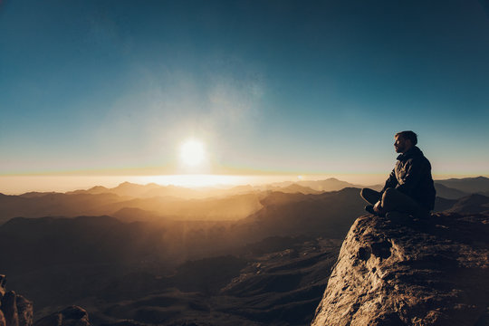 Man sits in a pose of yoga on Mount Sinai and meditates against background of sunrise.
