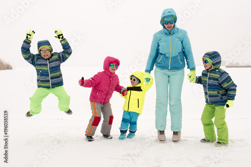 283c954e8e2 Happy young mother in blue ski suit wearing sunglasses with funny children  in bright winter clothes
