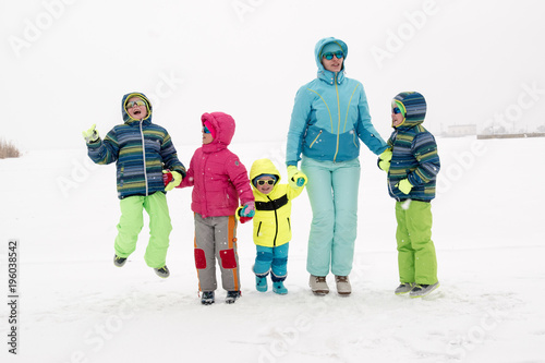4bee7089d76 Happy young mother in blue ski suit wearing sunglasses with funny children  in bright winter clothes jumping for joy on shore of icy lake.