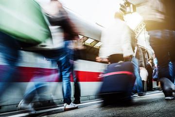 Menschen eilen einen Bahnsteig entlang