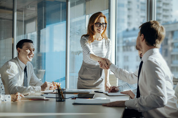 Best cooperation. Charming young woman carrying out a meeting with her companys business partners and shaking hands with a new one