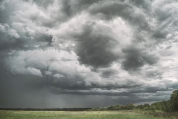 Large picturesque rain clouds over fields and meadows of Russia
