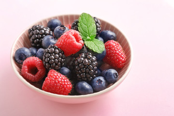 Berry (raspberry, blueberry, blackberry) fruits bowl on a pastel background.
