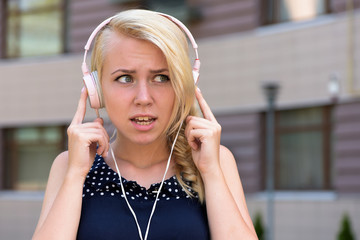 Woman with confused face listening music. Woman with blonde hair