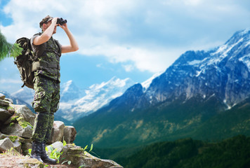 soldier with backpack looking to binocular Wall mural