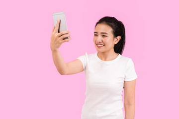 Cute asian woman taking selfie shot with smart phone camera, beautiful posting, nice smile, social media teenage girl, white shirt, pink background