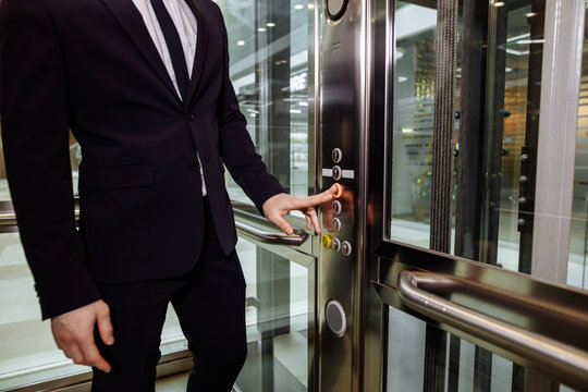 hand reaches for button of the elevator call.