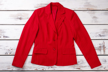 Red women jacket suit. Flat lay, fancy female jacket. Bright wooden desks surface background.
