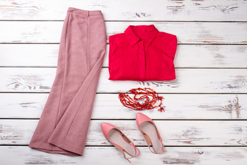 Summer collection women clothes outfit, flat lay. Red folded shirt, ling skirt, pair of shoes and necklace.