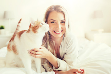 Fototapete - happy young woman with cat in bed at home