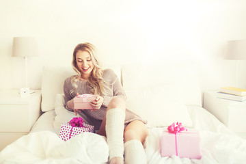 Fototapete - happy young woman with gift boxes in bed at home