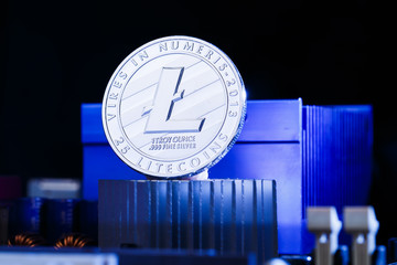 Image of crypto currency litecoin and processor on blue background