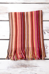 Fashionable striped woolen scarf. Vertical colourful stripes. White wooden desks surface background.
