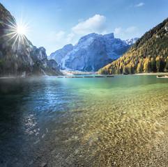 Idyllischer Bergsee von Felsen umgeben mit Wald und weißer sternenförmiger Sonne