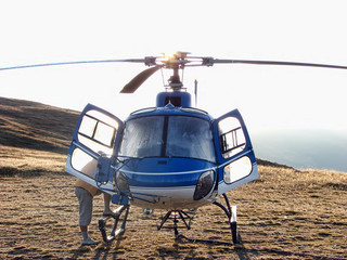 The pilot and blue helicopter on the mountain