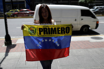 A woman holds a Venezuelan flag as opposition supporters gather in front of the United Nations offices in Caracas