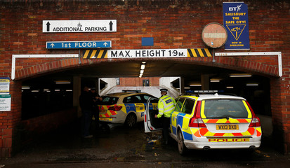 Police officers work at a supermarket near the bench where former Russian intelligence officer Sergei Skripal and his daughter Yulia were found poisoned, in Salisbury