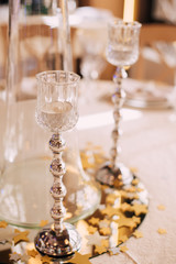 Festive table with a glass candlestick on a silver high stand