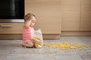 Toddler making mess with bag of cereal
