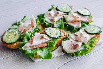 Sandwiches with cucumbers and prosciutto on the board