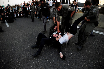 Israeli ultra-Orthodox Jewish men is being carried away by police after blocking a main road in Israel during a protest against the detention of a member of his community who refuses to serve in the Israeli army, in Bnei Brak