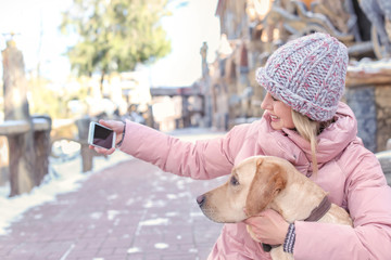 Woman taking selfie with her cute dog outdoors on winter day
